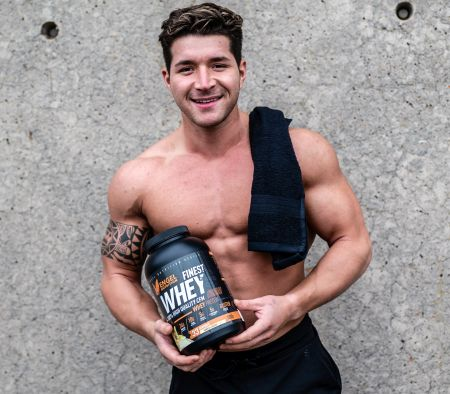 Fitness Athlet hält Finest Whey Protein
