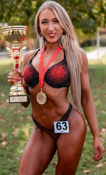 Bikini Athletin Luisa Schipp nach erfolgreichem Wettkampf mit Pokal